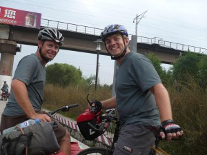 Riding into the Qinghuangdao, Kevin and Sean take a break from the pollution to pose for a picture.